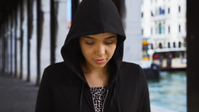 lonely depressed latin female in hoodie sweatshirt stands near grand canal - sweatshirt stock videos & royalty-free footage