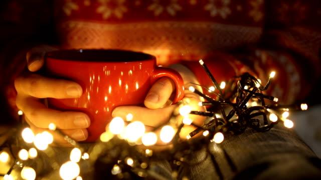 vídeos y material grabado en eventos de stock de chica solitaria sosteniendo una taza de café en la víspera de navidad - brazo humano