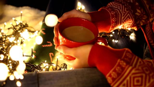 vídeos y material grabado en eventos de stock de chica solitaria sosteniendo una taza de café en la víspera de navidad - miembro humano
