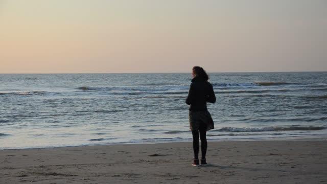 vídeos de stock e filmes b-roll de menina solitária na praia - reclusão