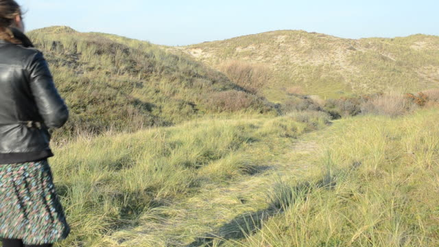 Lonely girl walking on the dunes