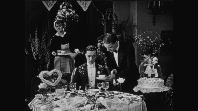 1920 lonely groom (buster keaton) sits by alone at a table decorated for him and his bride - domestic staff stock videos and b-roll footage
