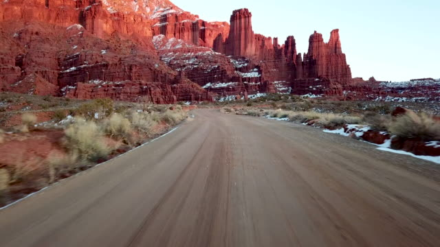 lonely highway near moab utah  fisher towers at dusk drone shot - moab utah stock videos & royalty-free footage