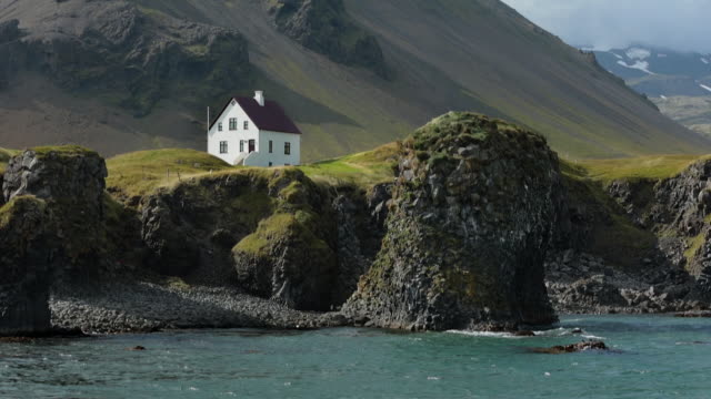lonely house standing on rock at the bottom of mountain, iceland. - scandinavian culture stock videos and b-roll footage