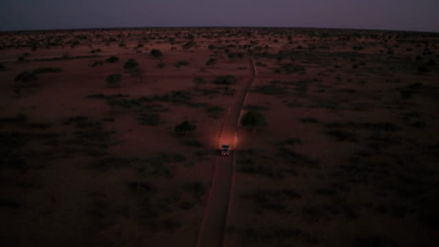 a lonely  is driving through the kalahari desert at night - sand dune stock videos & royalty-free footage