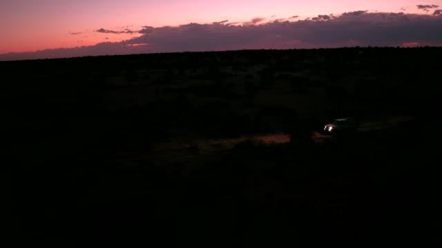 ein einsamer ist durch die kalahari-wüste fahren in der nacht - autoscheinwerfer stock-videos und b-roll-filmmaterial