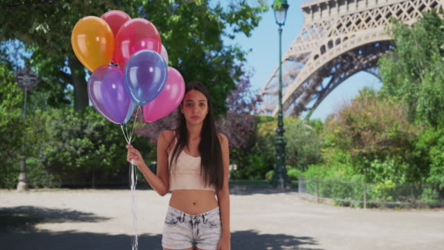 Lonely Latina holds a bunch of balloons in front of the Eiffel Tower