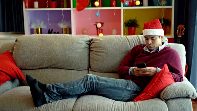 4k lonely man playing smart phone in a living room at home during christmas - loneliness stock videos & royalty-free footage
