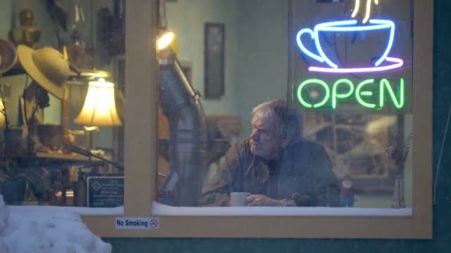 vídeos de stock, filmes e b-roll de lonely man sits in empty coffee shop window with open sign - evitar os outros