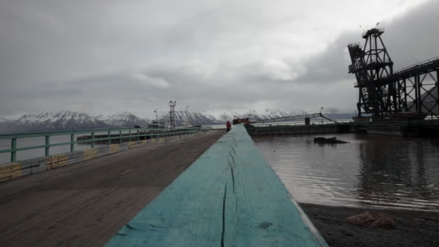 lonely man walking at the old harbor of the abandoned russian settlement and coal mining community pyramiden on the archipelago of svalbard, norway - スヴァールバル諸島およびヤンマイエン島点の映像素材/bロール