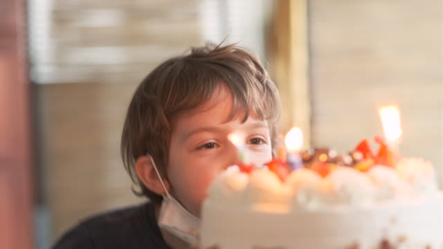 vídeos de stock e filmes b-roll de lonely pensive serious little boy wearing a protective face mask looking at his birthday cake - candlelight