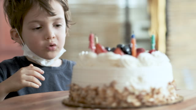 lonely pensive serious little boy wearing a protective face mask looking at his birthday cake - birthday cake stock videos & royalty-free footage
