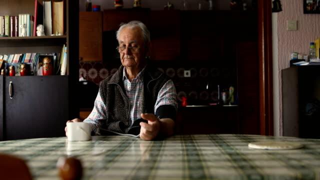lonely retiree measuring blood pressure at home - blood pressure gauge stock videos & royalty-free footage