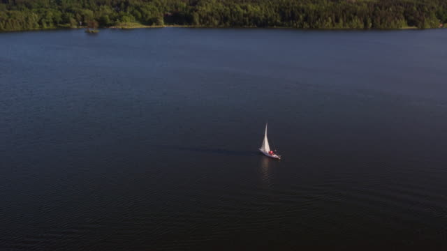 aerial: a lonely sailboat crossing a lake - resa stock videos & royalty-free footage