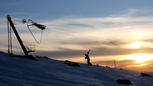 lonely skier climbing a slope beneath an abandon ski lift - ski lift stock videos & royalty-free footage