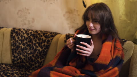 vídeos y material grabado en eventos de stock de lonely woman in warm cozy plaid drinks tea and thinks about life - tartán