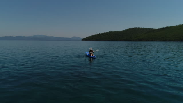 湖や海のカヤックの孤独な女性。幸せな成熟した女の夏の日に湖や海でカヌーします。 - カヤック点の映像素材/bロール