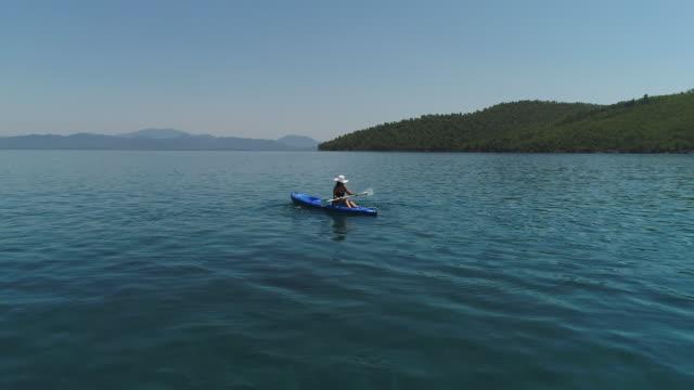 湖や海のカヤックの孤独な女性。幸せな成熟した女の夏の日に湖や海でカヌーします。 - カヤッキング点の映像素材/bロール