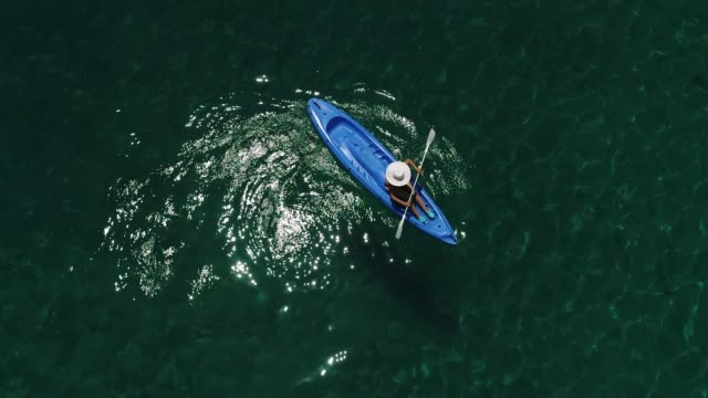 lonely woman kayaking on a lake or sea. happy mature woman canoeing in a lake or sea on a summer day. - kayak video stock e b–roll