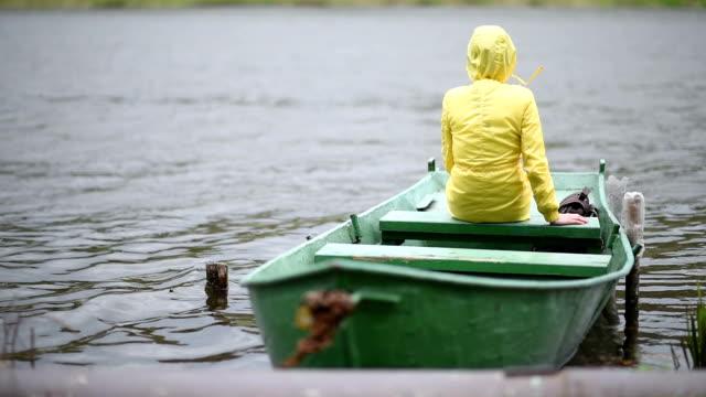 vídeos de stock, filmes e b-roll de lonely woman on the boat - capa de chuva