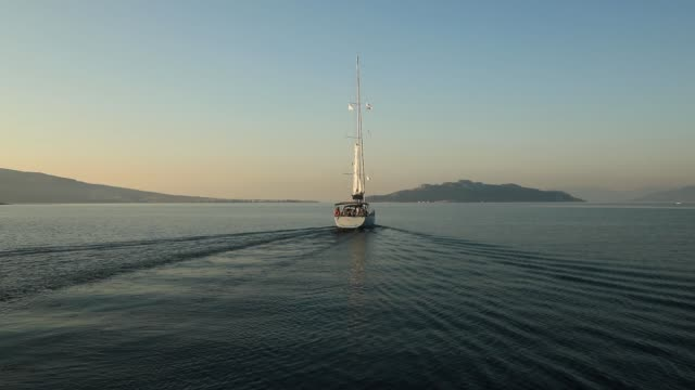 lonely yacht sailing on silent sea. aegina island, greece - ヨット点の映像素材/bロール