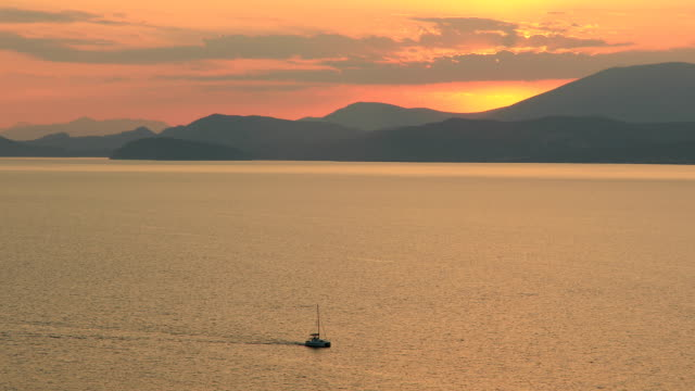 Lonely yacht sailing on silent sea at sunset. Aegina Island, Greece