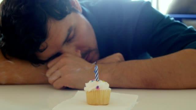 Eenzame jonge man uitblazen verjaardag kaars op de cupcake en het maken van een triest gezicht