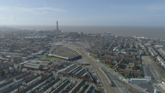 long aerial view following a train arriving at blackpool railway station with tower and sea view - ブラックプール点の映像素材/bロール