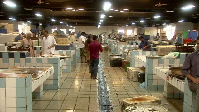 pan long aisle of ceramic tiled booths at indoor fish market / manama, bahrain - short phrase stock videos & royalty-free footage