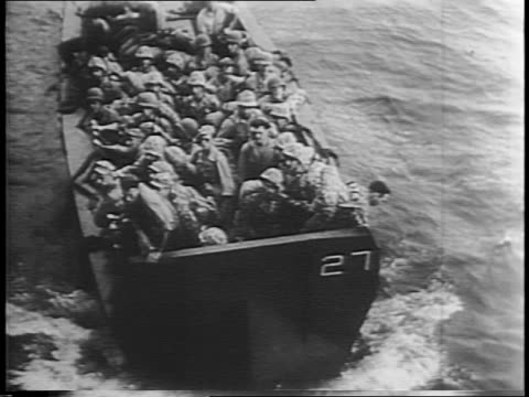 Long beach and palm trees / soldiers loading cargo onto landing barges headed for the island Bougainville on Guadalcanal / soldiers on a barge on the...