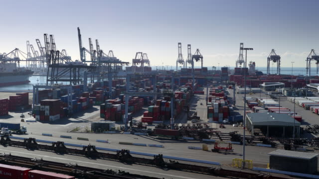 t/l long beach container terminal in long beach california. cranes move shipping containers, trucks and cars fly by in the foreground. in the background is the sea. clouds pass slowly by - sea robin stock videos & royalty-free footage