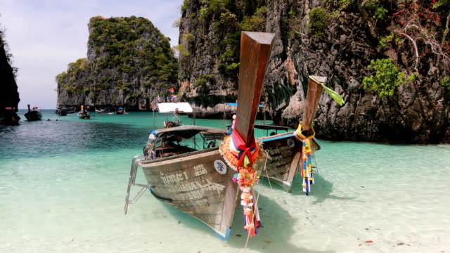 long boat and blue water at maya bay in phi phi island, krabi thailand - mayan stock videos & royalty-free footage