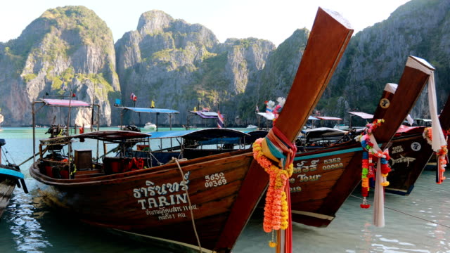 long boat and blue water at maya bay in phi phi island, krabi thailand - longtail boat stock videos & royalty-free footage