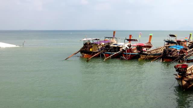 long boats and tropical beach, railay beach, krabi, thailand. - railay beach stock videos and b-roll footage