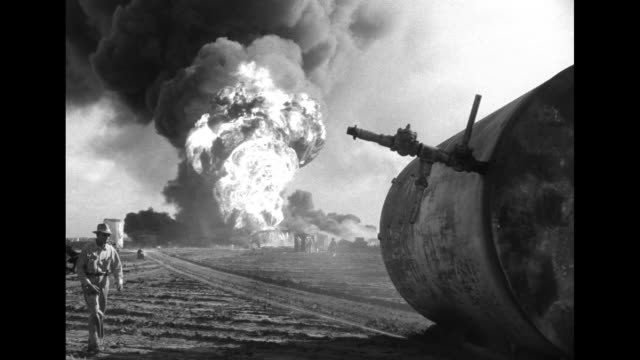 vídeos de stock e filmes b-roll de long boom with hose attached sprays sparse amount of water as oil well fire emits clouds of black smoke in background; men stand by the boom with a... - caterpillar inc
