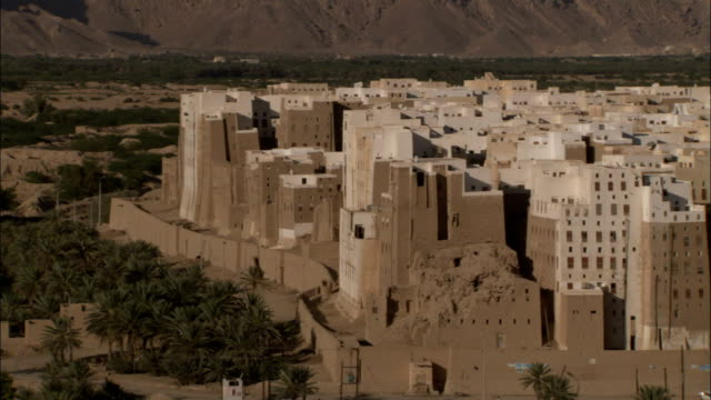 A long brick wall encompasses the mud-brick town of Shibam in Yemen.
