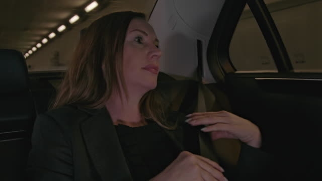 stockvideo's en b-roll-footage met long brown haired mid 40 mature business woman enjoys getting chauffeured in a limousine - driving through a city tunnel in a taxi and fastening seat belt - veiligheidsgordel