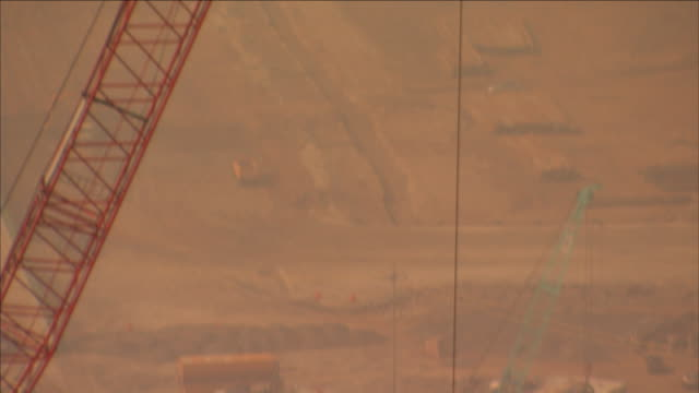 vídeos de stock e filmes b-roll de a long cable hangs from a tower crane at a dusty construction site. - cable