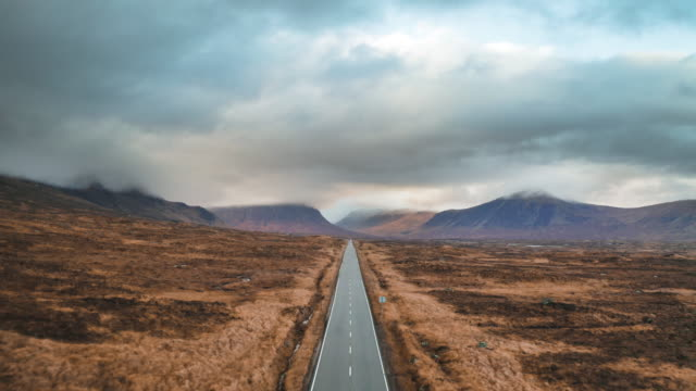 vídeos de stock e filmes b-roll de long country road in the scottish highlands - nublado