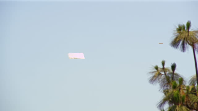 long distance shot of airplane carrying advertisement - pulling stock videos & royalty-free footage