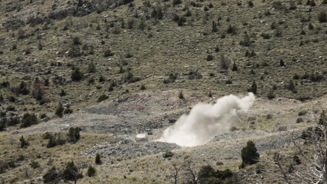 Long distance shot of explosion in training exercise; sound follows visual.