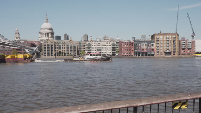 a long dolly shot along the thames river, following a boat going under the millennium foot bridge - river thames stock videos & royalty-free footage