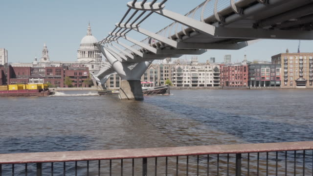 a long dolly shot along the thames river, following a boat going under the millennium foot bridge - 50 seconds or greater stock videos & royalty-free footage