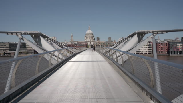 a long dolly shot over the millennium footbridge towards st paul's cathedral, london - footbridge stock videos & royalty-free footage