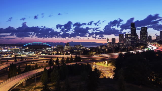 Long exposure EWS day-to-night time lapse of highways at sunset, including views of downtown Seattle's skyline, CenturyLink Field, and Elliot Bay