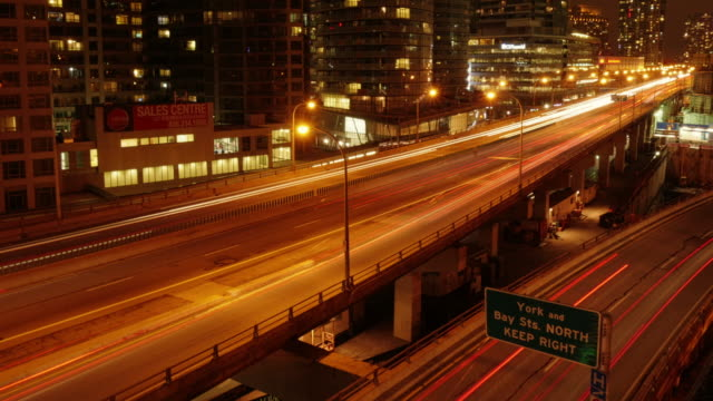 long exposure night time timelapse shot overlooking gardiner expressway in toronto with light streaks from vehicles. - spoonfilm stock-videos und b-roll-filmmaterial