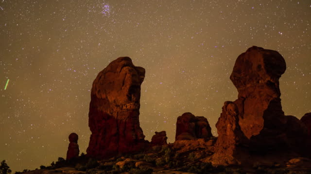 a long exposure time lapse showing stars moving across the night sky in the garden of eden arches national park utah - moab utah stock videos & royalty-free footage