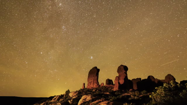 a long exposure time lapse showing stars moving across the night sky in the garden of eden arches national park utah - arches national park stock videos & royalty-free footage