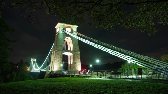 a long exposure timelapse of cars driving across clifton suspension bridge leaving light trails at night - light trail stock videos & royalty-free footage