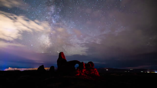 vídeos de stock e filmes b-roll de long exposure timelapse of clouds clearing above turret arch in arches national park, revealing the spectacular milky way - long exposure